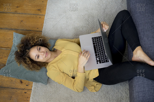 Smiling young woman lying on the floor at home using laptop