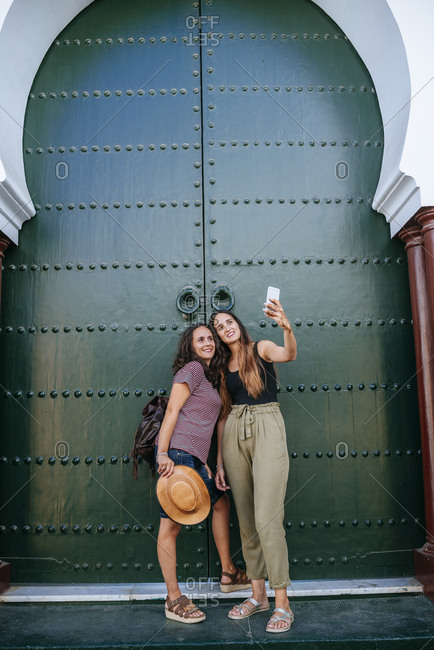 Morocco- Chefchaouen- two women taking selfie with smartphone in front of green portal