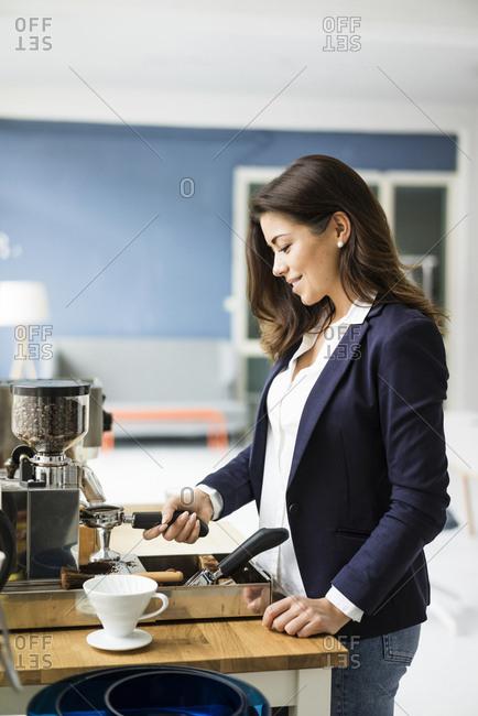 Smiling businesswoman preparing espresso with espresso machine in a loft