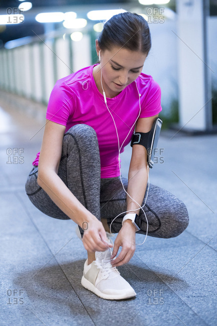 Young woman in pink sportshirt listening to music and tying her sneakers