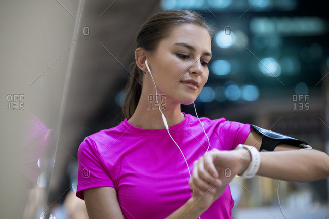 Young woman in pink sportshirt listening to music and checking her smartwatch