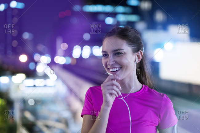 Smiling young woman in pink sportshirt listening to music in city at night