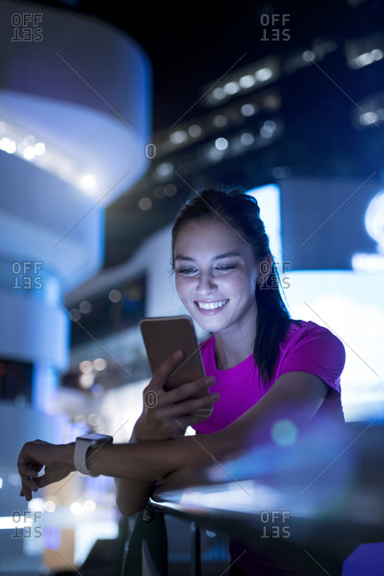 Young woman in pink sportshirt checking her smartphone in city at night