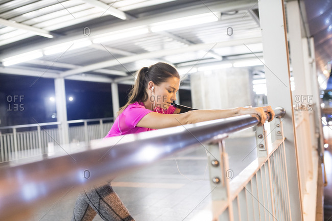 Young woman in pink sportshirt stretching in modern metro station at night