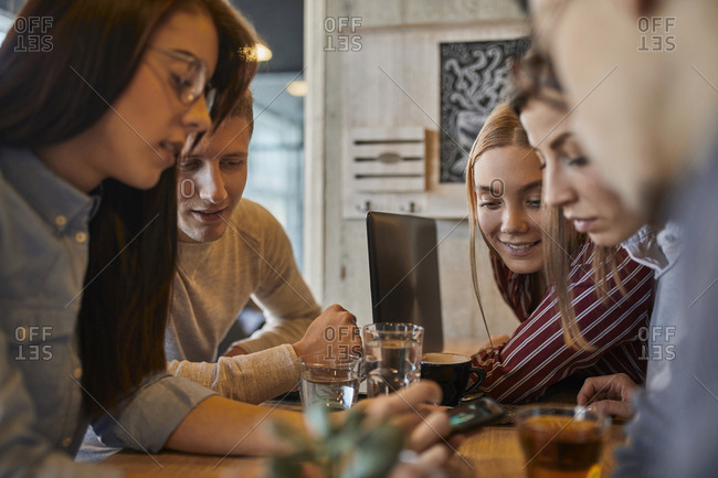 Group of friends sitting together in a cafe sharing smartphone