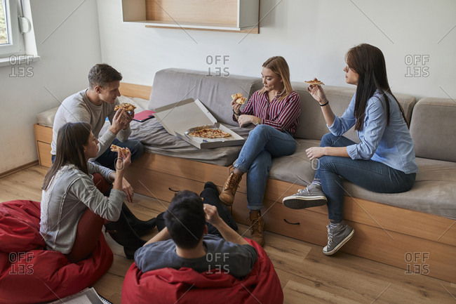 Group of students in dormitory eating pizza together