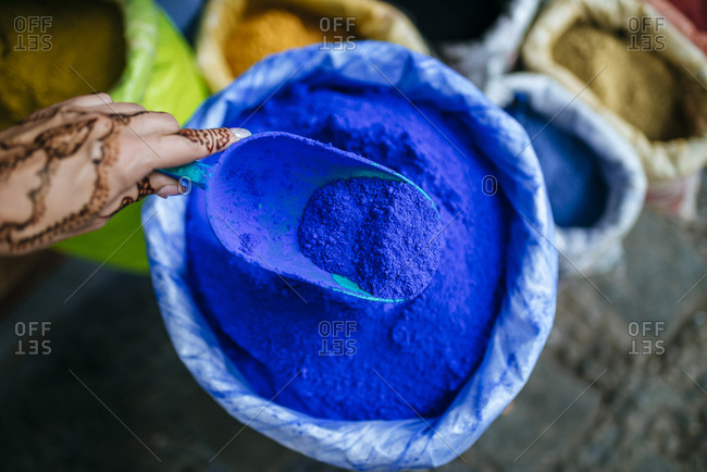 Morocco- Chefchaouen- woman's hand painted with henna tattoo holding ladle with blue pigments