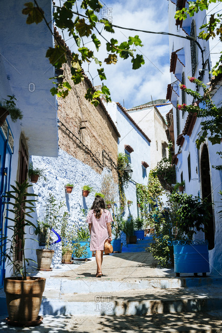 Morocco- Chefchaouen- back view of woman walking alley upstairs