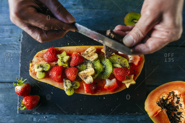 Close-up of man's hands cutting chocolate over half papaya garnished with pieces of banana- kiwi and strawberries