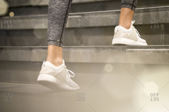 Close up of female legs with white sport sneakers running up the stairs
