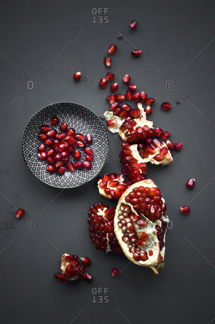 Pomegranate and pomegranate seeds in bowl