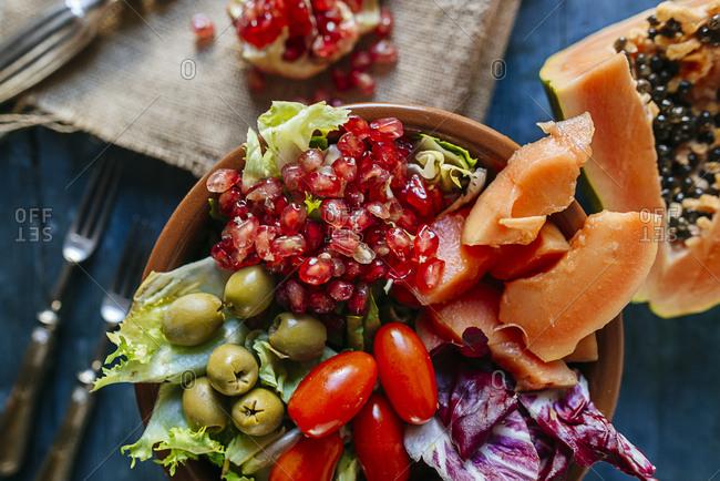Close-up of papaya salad- pomegranate- lettuce- tomato- olives and endive in bowl