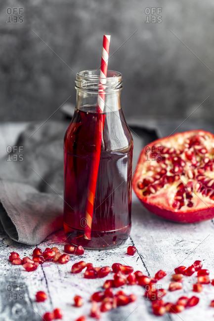 Glass bottle of pomegranate juice and sliced pomegranate