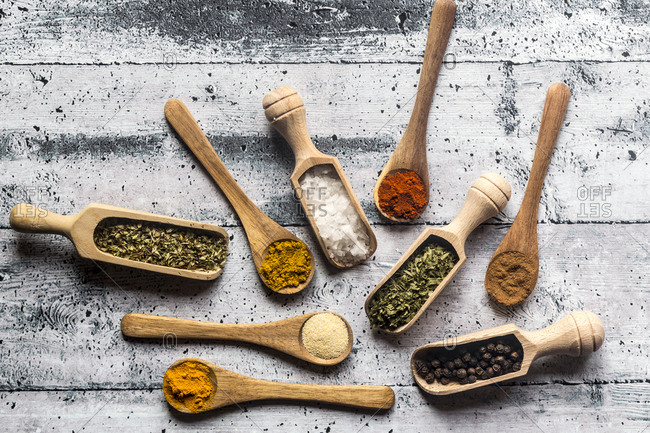 Spices- curry- chilli- cinnamon- curcuma- garlic- parsley- oregano- salt and pepper on wooden spoons