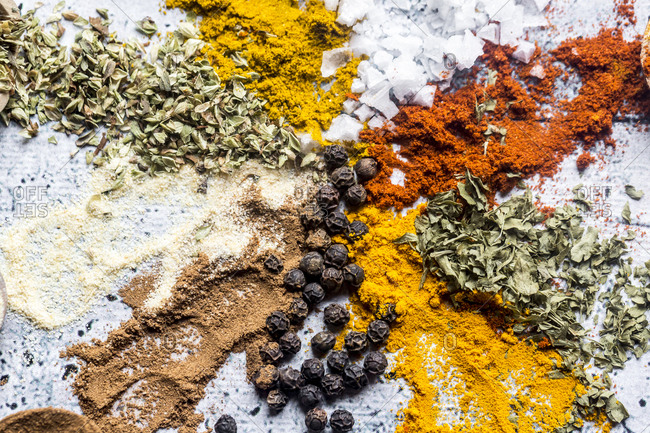 Spices- curry- chilli- cinnamon- curcuma- garlic- parsley- oregano- salt and pepper on wood