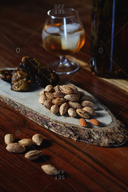 Almonds and dried figs on wooden serving board
