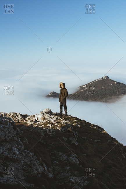 Anonymous traveler in outerwear standing on rocky edge with background of mountain peak in clouds.