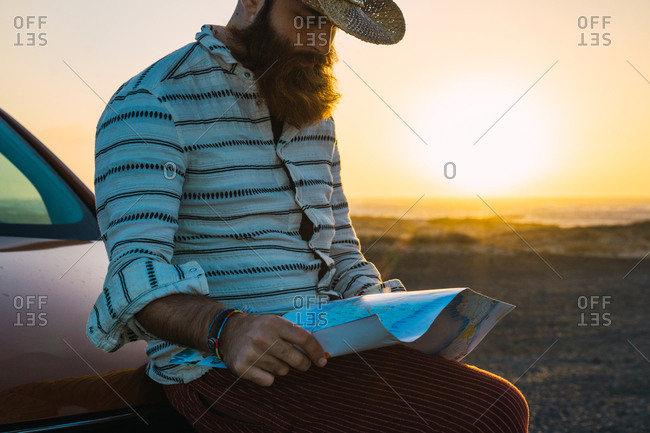 Handsome man with gorgeous beard wearing straw hat and looking at map sitting on car hood.
