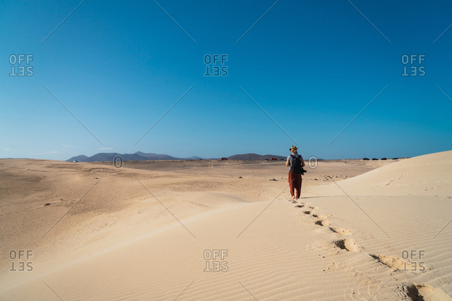 Back view of man with backpack exploring endless sandy terrains in sunlight.