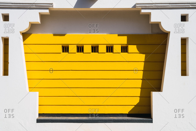 Exterior shot of white ornamental facade with yellow paneling in bright sunlight.