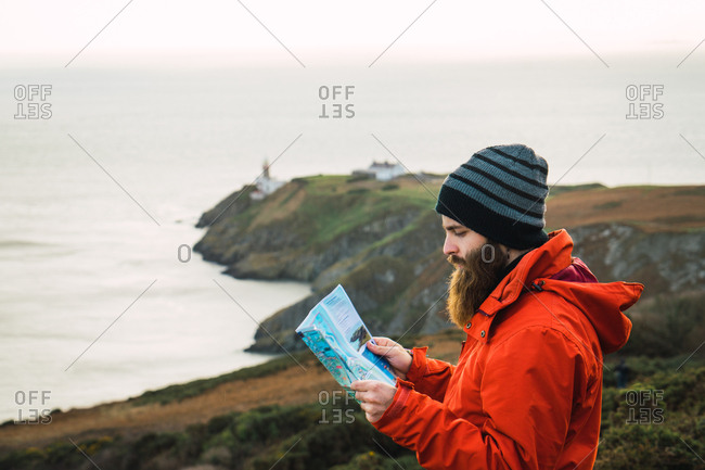 Bearded man navigating in hills