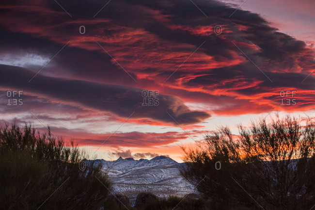 Dramatic sunset at Gredos mountain range with red clouds and snowy mountains