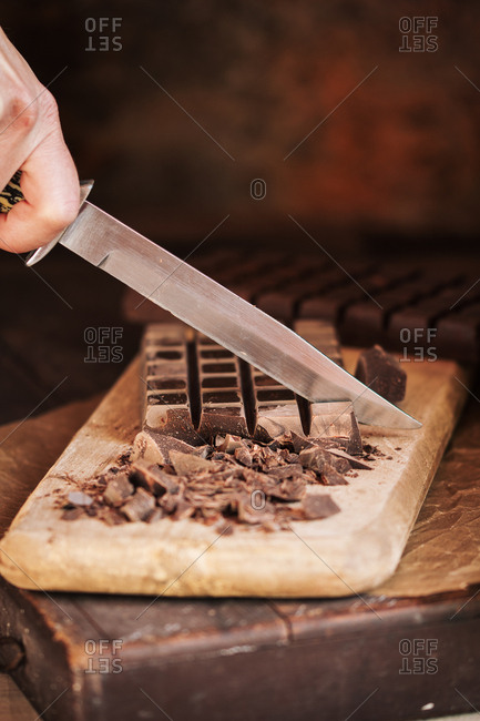 Woman hand cutting chocolate tablet