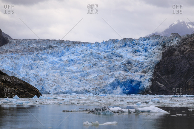Ice pack and blue ice face of South Sawyer Glacier, mountain backdrop, Stikine Icefield, Tracy Arm Fjord, Alaska, United States of America, North America