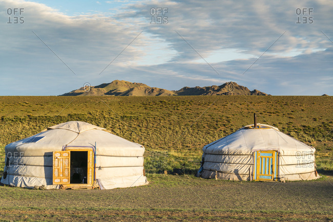 Two Mongolian nomadic gers and mountains in the background, Bayandalai district, South Gobi province, Mongolia, Central Asia, Asia