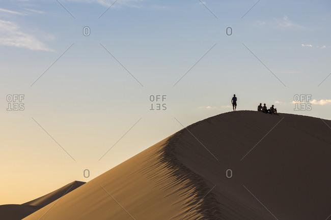 People in silhouette on Khongor sand dunes in Gobi Gurvan Saikhan National Park, Sevrei district, South Gobi province, Mongolia, Central Asia, Asia