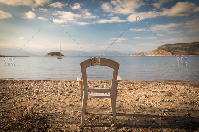 Old Broken Chair on a Rocky Beach in front of the Aegean Sea on a Beach Near Nafplio in the Peloponnese