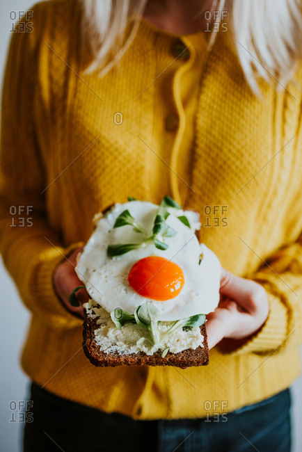 Woman holding toast topped with an egg
