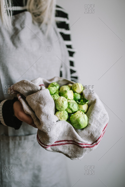 Woman carrying a bunch of brussel sprouts in a towel
