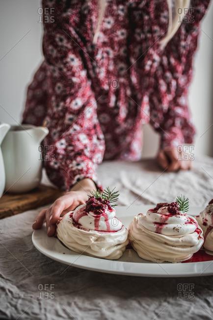 Woman grabbing a mini pavlova with raspberries