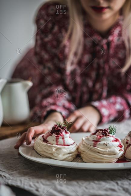 Woman reaching for a mini pavlova with raspberries