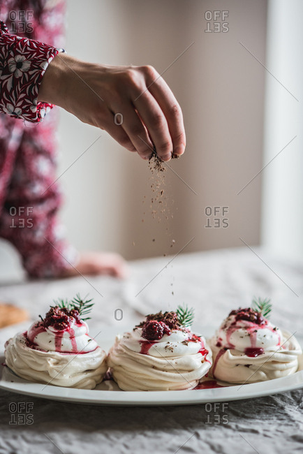 Woman topping mini pavlovas with chocolate