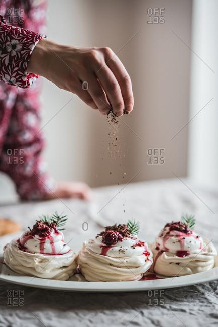 Woman topping mini pavlovas with chocolate