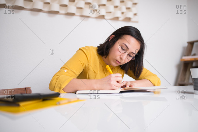 Woman sitting at table writing in a journal