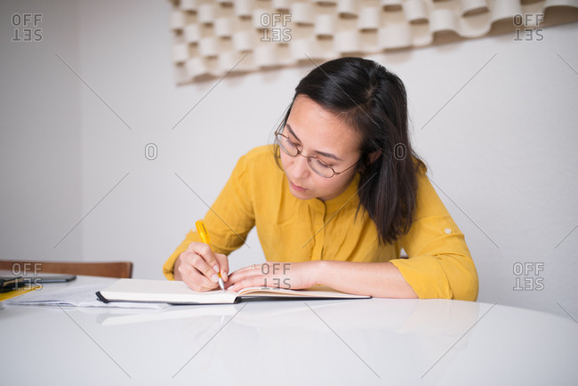 Woman sitting at table writing in a notebook