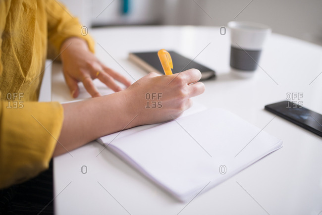 Close up of a woman writing in a journal