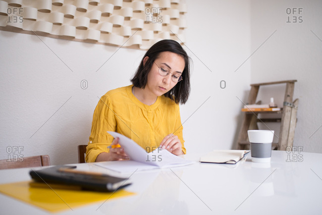Woman reading and writing in a notebook