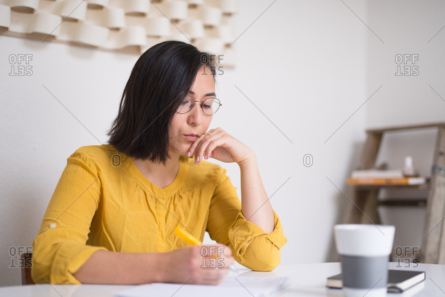 Woman sitting at table writing poetry