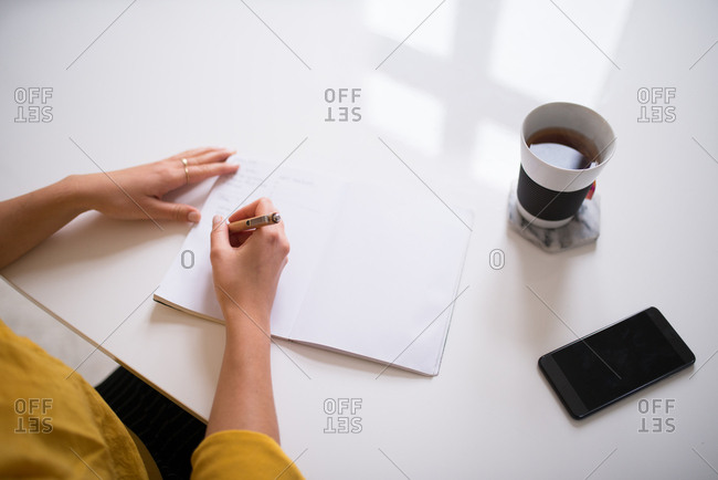 Overhead view of woman sitting at table writing in her journal