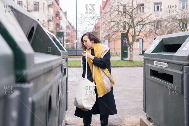 Woman sorting her trash in bins