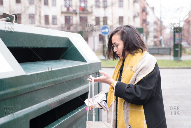 Woman placing her recycling in bins