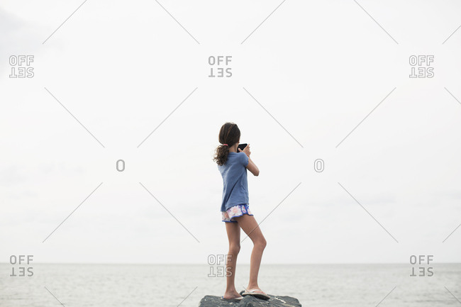 Young girl at beach taking photo of the ocean