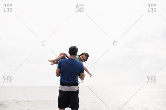 Little girl laughing as daddy lifts her up at the beach