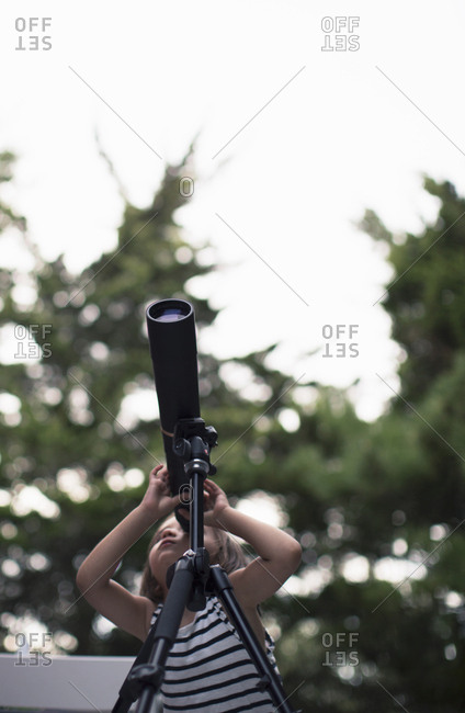 Young girl adjusting focus as she looks through telescope