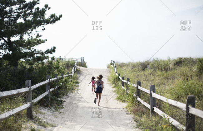 Young girls running along a path through the dunes to the beach