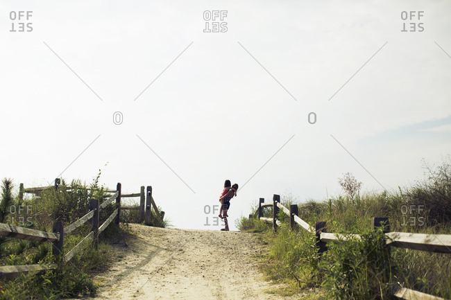 Girl holding her younger sister as they look at the beach and the sea from top of the dune
